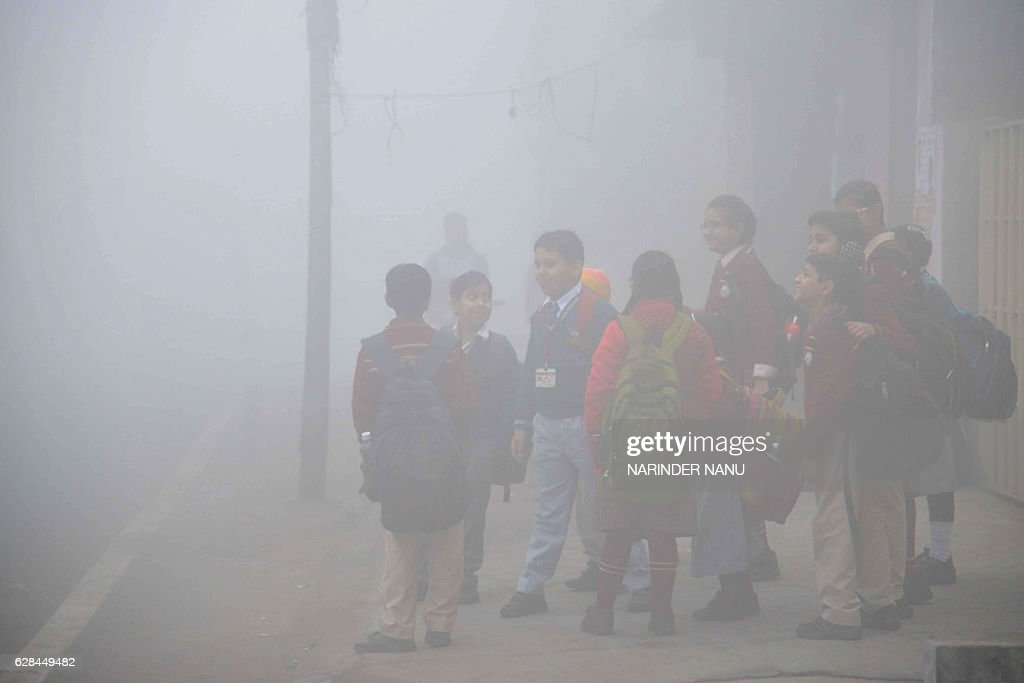Indian school children wait for their bus on their way to school on a cold and foggy morning in Amritsar on December 8 2016 / AFP / Narinder NANU