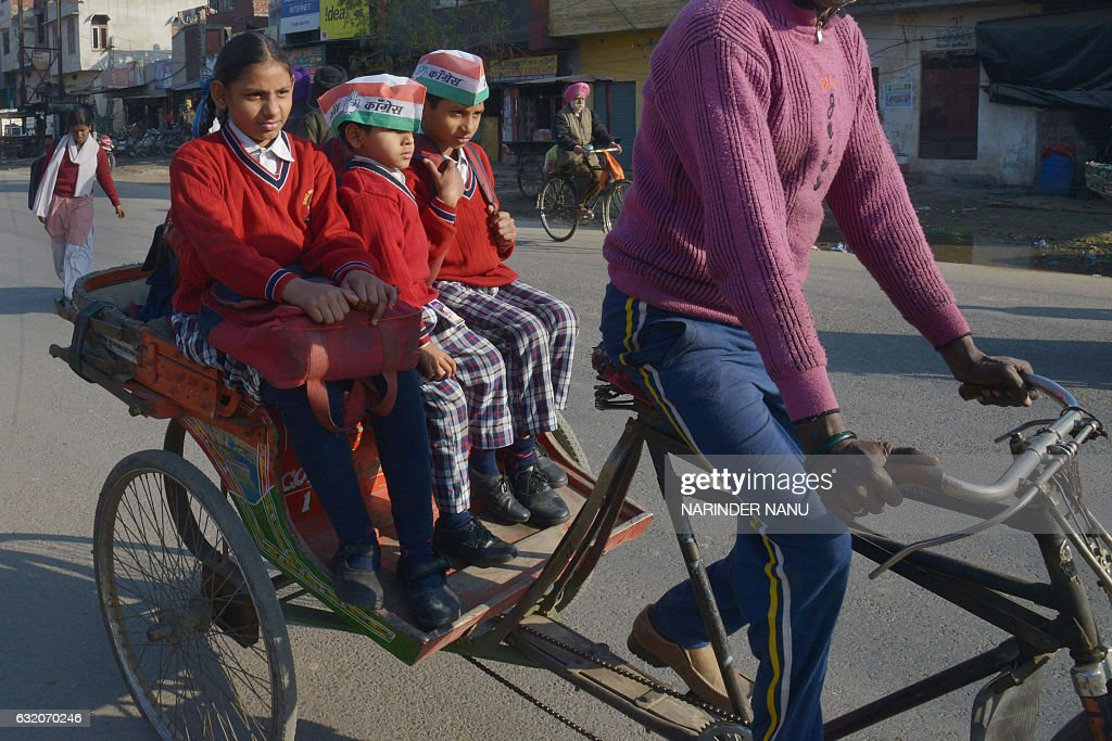 Indian school children wear caps with Congress party symbols as they travel on a cyclerickshaw in Amritsar on January 19 2017 / AFP / Narinder NANU