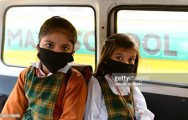 Indian school children wear masks as they sit inside a school cab as schools reopen after three days of closure due to smog in New Delhi on November...