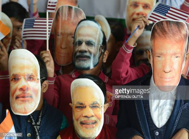 Indian school children wearing masks of Indian Prime Minister Narendra Modi and US President Donald Trump pose for a picture at Bright Academy school...