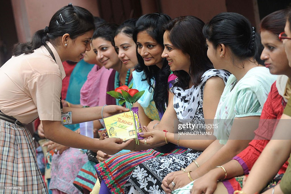 Indian school girl Mansi presents a rose and greeting card to her school teacher during celebrations of `Teacher`s Day` at a public school in...