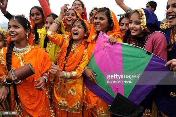 Indian school girls dressed in outfits of the Punjabi traditional folk dance the Giddha watch kites flying on the eve of Basant Panchami the Festival...