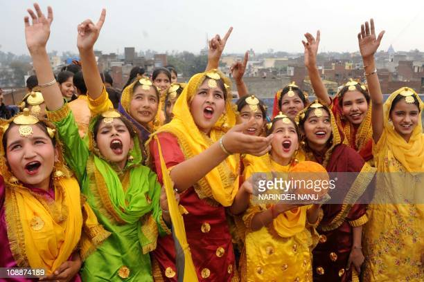 Indian school girls dressed in Punjabi traditional folk Giddha outfits smile as they fly kites on the eve of Basant Panchami the Festival of Spring...