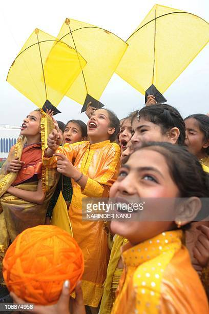 Indian school girls dressed with Punjabi traditional folk Giddha outfits smile as they fly kites on the eve of Basant Panchami the Festival of Spring...