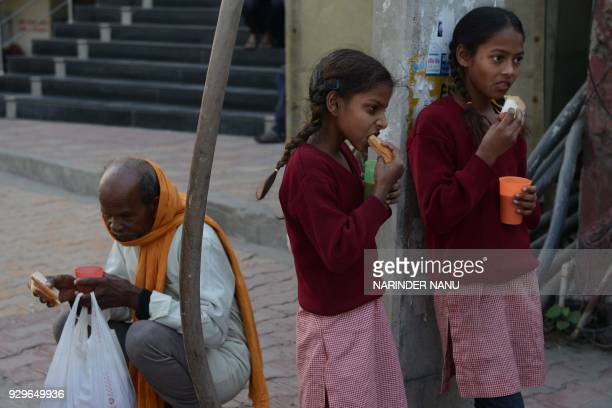 Indian school girls eat bread and drink tea donated by volunteers at a roadside in Amritsar on March 9 2018 / AFP PHOTO / NARINDER NANU