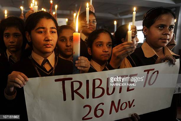 Indian school girls hold candles and a sign at DAV Public school in Amritsar on November 26 2010 in tribute to those killed in the 26/11 Mumbai...