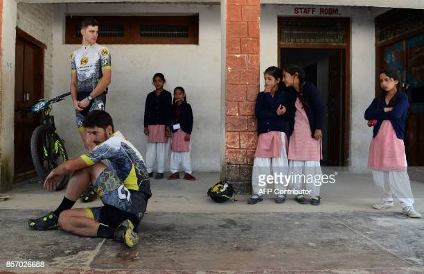 Indian school girls look at mountain bike riders resting after competing in the Hero MTB Himalaya mountain bike race at the rest area in Bagshed...