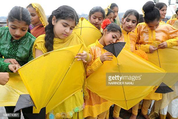 Indian school girls prepare kites on the eve of Basant Panchami the Festival of Spring in Amritsar on February 7 2011 Kiteflying is the major and...
