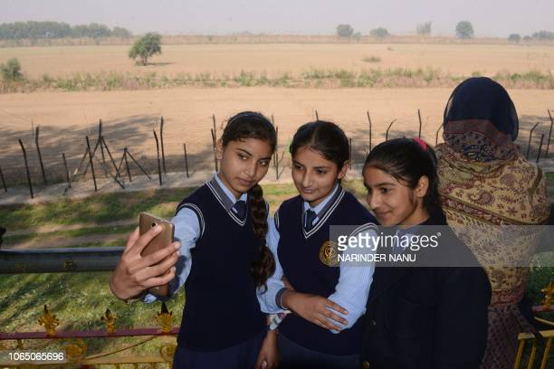 Indian school girls take selfie after offering prayers towards the Gurdwara Kartarpur Sahib which is situated in Pakistan from Indian side at Dera...