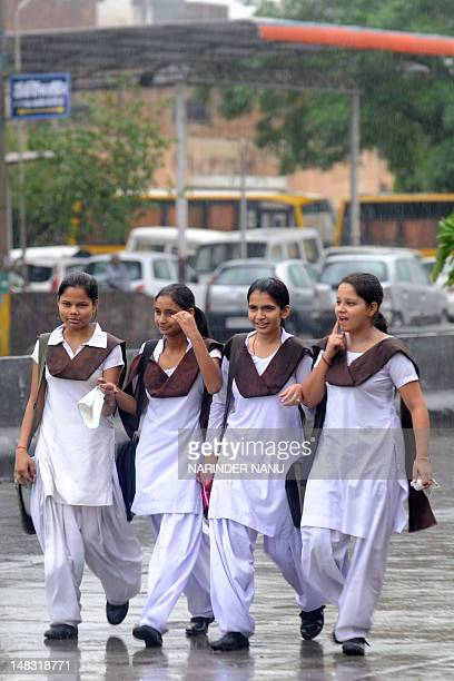 Indian school girls walk through a rain downpour in Amritsar on July 14 2012 Heavy rains which fell in several areas of northern India have brought...