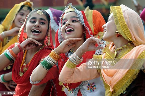 Indian school girls wearing traditional Punjabi dresses dance the 'giddha' folk dance during celebrations for India's Independence Day at the...