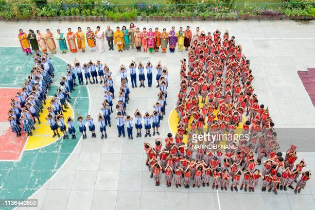 TOPSHOT Indian school students and teachers stand in the shape of the number '100' and the Jallianwala Bagh Martyrs' Memorial as they pay tribute a...