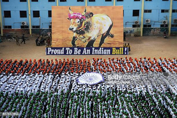Indian school students form the national flag alongside a poster supporting the Jallikattu bulltaming festival a ban on which has been overturned...