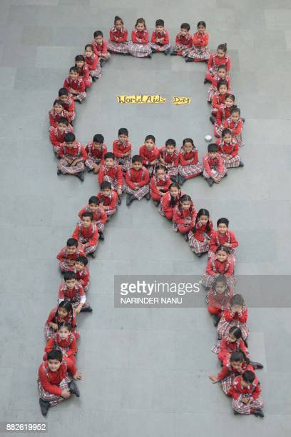 TOPSHOT Indian school students pose for a photograph as they sit in the shape of a ribbon during an awareness campaign on the eve of the World AIDS...