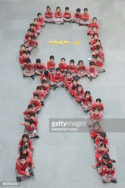 Indian school students pose for a photograph as they sit in the shape of a ribbon during an awareness campaign on the eve of the World AIDS Day in...