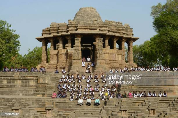 Indian school students take part in a yoga session to mark International Yoga Day at the Sun Temple in Modhera near Mahesana town some 100km from...