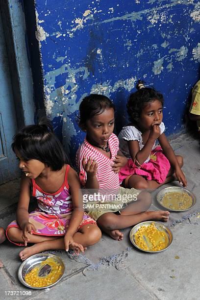 Indian schoolchildren at Jahangirpura Shala Number 2 which is run by the Ahmedabad Municipal Corporation eat their free midday meal in Ahmedabad on...