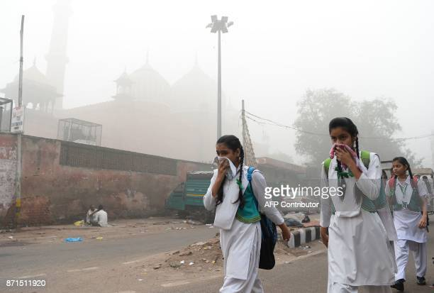 TOPSHOT Indian schoolchildren cover their faces as they walk to school amid heavy smog in New Delhi on November 8 2017 Delhi shut all primary schools...