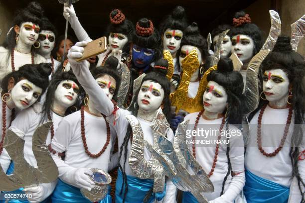 TOPSHOT Indian schoolchildren dressed as Hindu God Lord Shiva pose for a 'selfie' ahead of performing a routine during an annual school function in...