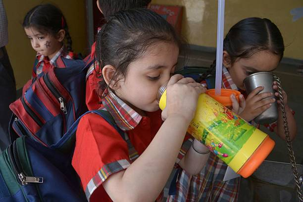 Indian schoolchildren drink water from bottle during a hot afternoon at a school in Amritsar on May 18 2016 Summer conditions on May 18 saw...