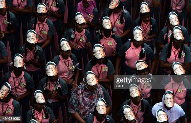 Indian schoolchildren holds masks with the face of Microsoft founder and philanthropist Bill Gates to mark his 60th birthday at a school in Chennai...
