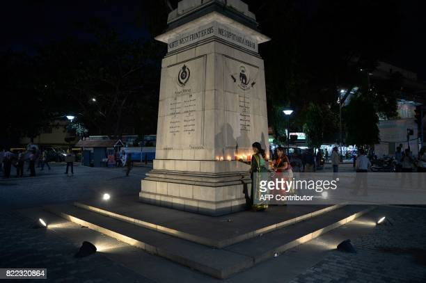 Indian schoolchildren place candles on a war memorial in Bangalore on July 25 on the eve of the anniversary of the end of the 1999 Kargil War between...
