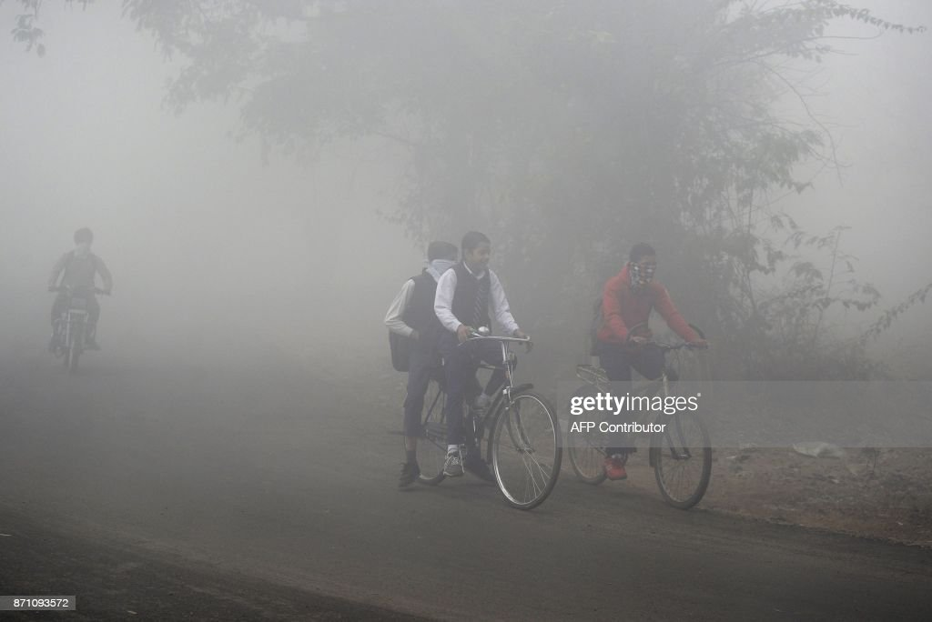 Indian schoolchildren ride their bikes to school in dense fog and air pollution in Jalandhar on November 7 2017 India`s Central Pollution Control...