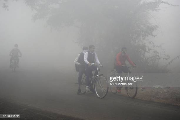 Indian schoolchildren ride their bikes to school in dense fog and air pollution in Jalandhar on November 7 2017 India's Central Pollution Control...