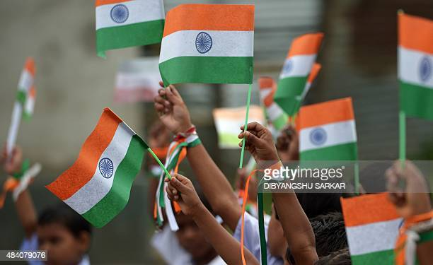 Indian schoolchildren wave national flags wait to perform during Independence Day celebrations at a school in Kolkata on August 15 2015 India...