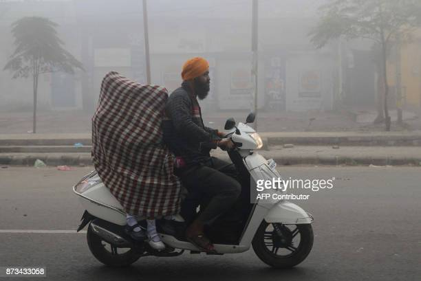 TOPSHOT Indian schoolgirls are covered in a sheet in an effort to protect themselves from heavy smog as they are driven to school on a scooter after...