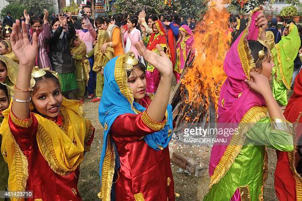 Indian schoolgirls clad in traditional Punjabi dress perform the giddha folk dance around a bonfire on the eve of the Lohri festival in Amritsar on...
