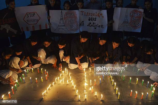 Indian schoolgirls light candles during a vigil at a school in Amritsar on November 16 following coordinated terror attacks in the French capital...