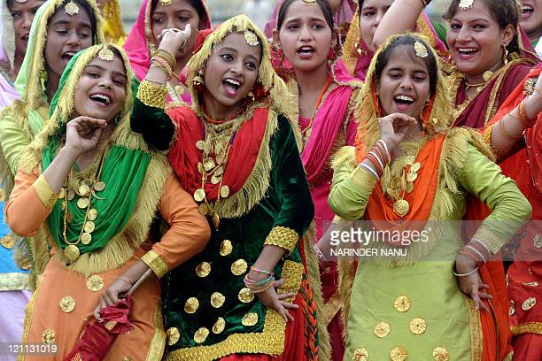 Indian schoolgirls perform the traditional 'giddha' dance as they attend an Independence Day parade rehearsal at the Gandhi Ground in Amritsar on...