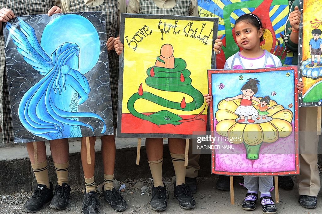Indian schoolgirls pose with placards during a protest march against various issues including female foeticide in Amritsar on March 23 2012 The march.