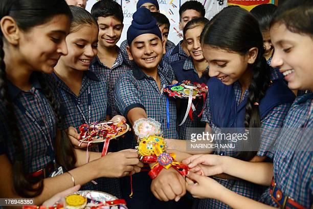 Indian schoolgirls tie a 'rakhi' sacred thread onto the wrist of a schoolboy on the eve of the Hindu festival Raksha Bandhan at a school in Amritsar...