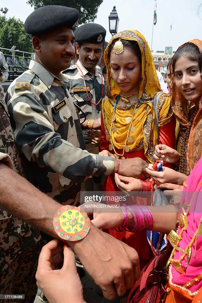 Indian schoolgirls tie a sacred thread or rakhi onto the wrists of Indian Border Security Force (BSF) personnel during the Raksha Bandhan festival at the India-Pakistan Wagah Border post on August 21, 2013. The ceremony topically involves a bracelet being tied by a sister to her brother's wrist, symbolising the sister's love and prayers for her brother's well-being, and the brother's vow to protect her.
