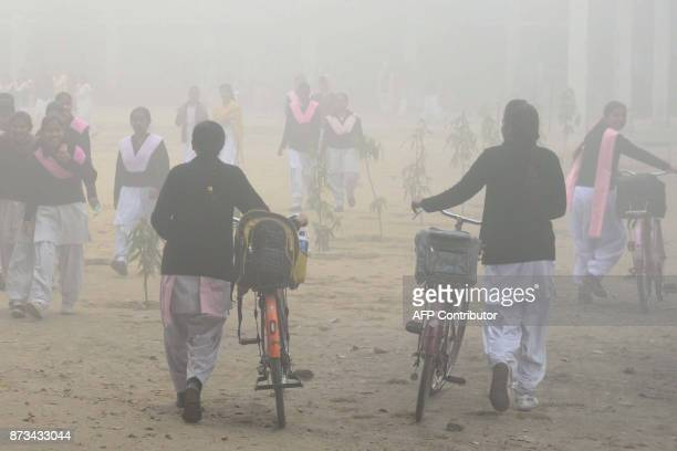 Indian schoolgirls walk to school after three days off due to heavy smog in Amritsar on November 13 2017 Large swathes of north India and Pakistan...