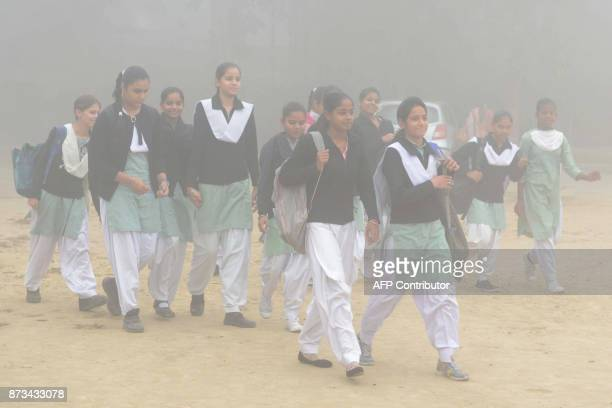 TOPSHOT Indian schoolgirls walk to school after three days off due to heavy smog in Amritsar on November 13 2017 Large swathes of north India and...