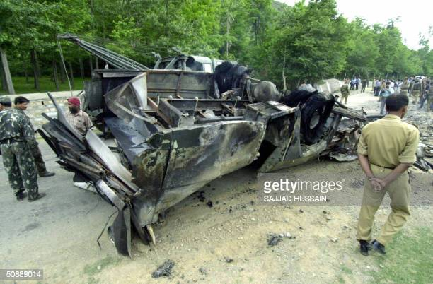 Indian security force personnel look at the smouldering wreckage of a Border Security Force bus damaged by a landmine explosion as it lies on the...