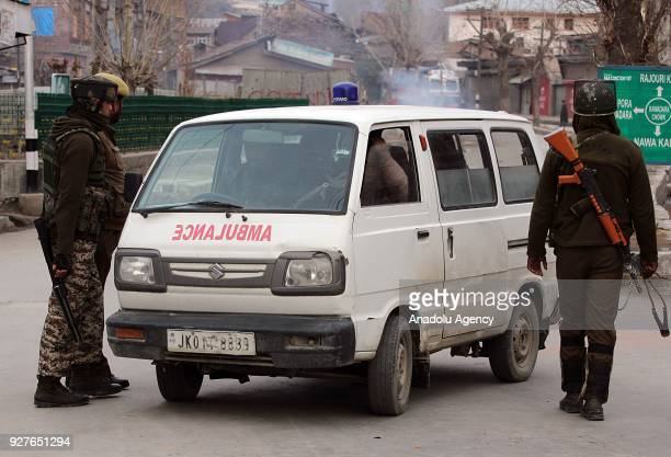 Indian security forces inspect an ambulance as Indians stage a protest after Indian army killed two militants and four civilians in Pahnoo village of...