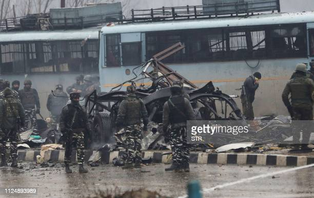 Indian security forces inspect the remains of a vehicle following an attack on a paramilitary Central Reserve Police Force convoy that killed at...
