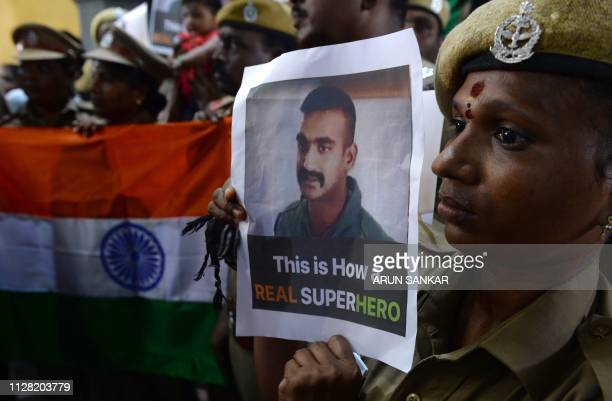 TOPSHOT Indian security forces pose with the national flag and pictures of Indian Air Force pilot Abhinandan Varthaman during an event to pray for...