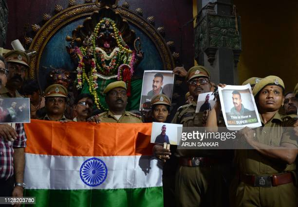 Indian security forces pose with the national flag and pictures of Indian Air Force pilot Abhinandan Varthaman during an event to pray for his return...