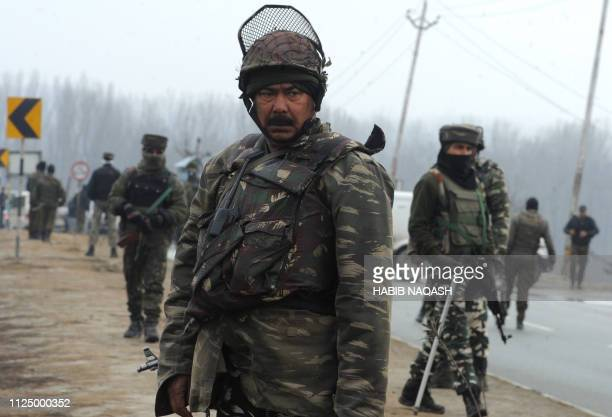 Indian security forces stand guard along the JammuSrinagar highway in Lethpora area in the town of Pampore some 30 kms South of Srinagar on February...