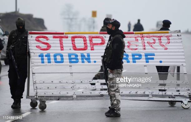 Indian security forces stand guard at a road block along the SrinagarJammu Highway following an attack on a paramilitary Central Reserve Police Force...