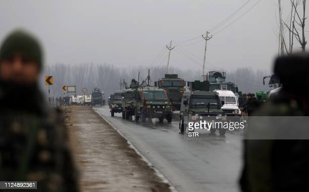 Indian security forces vehicles drive to the site of an attack on a paramilitary Central Reserve Police Force convoy that killed at least 16 troopers...