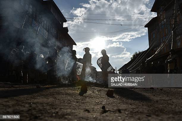 TOPSHOT Indian security forces watch Kashmiri protestors in Srinagar on August 29 2016 Authorities lifted a curfew in Indianadministered Kashmir...