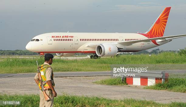 Indian security looks on as Air India's first Boeing 787 Dreamliner from Charleston USA arrives at Indira Gandhi International airport's terminal T3...