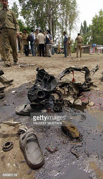Indian security personnel and bystanders gather at the scene of a bomb blast in Pulwamasome 30kms south of Srinagar 13 June 2005 At least seven...