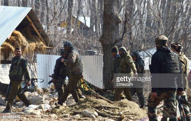 Indian security personnel carry a victim injured in a firefight through the scene of the gunbattle in Frisal village in Kulgam some 70 kms south of...